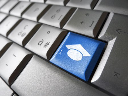 Online education and e-learning concept with graduation hat icon and symbol on a blue computer key for school and online educational business.